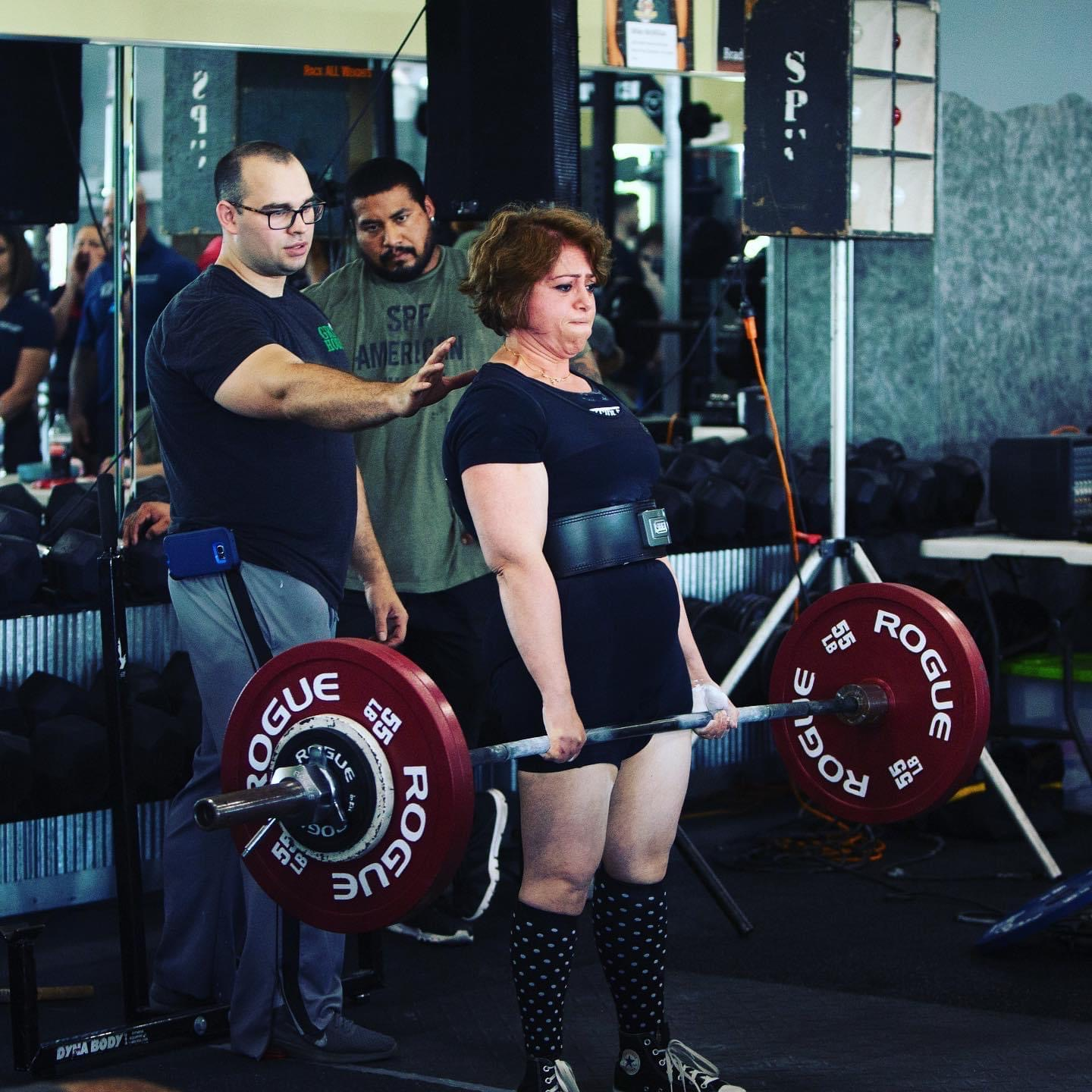 Champion powerlifter Anjuli Bhat-Mejia performs a move at a CrossFit competition while a spotter assists.